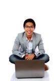 Uomo che si siede sul pavimento con il computer portatile Immagini Stock