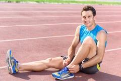 Uomo che si siede sul pavimento e che merletta le scarpe da tennis Fotografia Stock Libera da Diritti