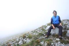 Uomo che si siede sul picco di montagna Immagini Stock