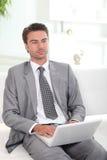 Uomo che si siede sul sofà Immagini Stock
