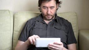 Uomo che si siede sul sofà con il computer della compressa video d archivio