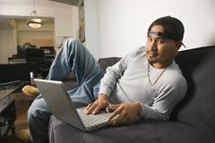 Uomo che si siede sul sofà per mezzo del computer portatile. Immagine Stock Libera da Diritti