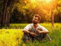 Uomo che si siede sull'erba al parco Fotografia Stock