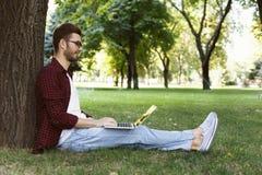 Uomo che si siede sull'erba con il computer portatile all'aperto Fotografia Stock Libera da Diritti
