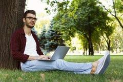 Uomo che si siede sull'erba con il computer portatile all'aperto Fotografie Stock Libere da Diritti