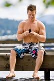 Uomo che si siede sull'invio di messaggi di testo del pilastro immagini stock libere da diritti