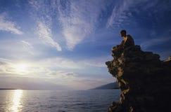 Uomo che si siede sull'oceano di trascuratezza della roccia Fotografie Stock