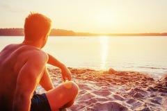 Uomo che si siede sulla sabbia al tramonto Fotografia Stock