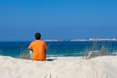 Uomo che si siede sulla sabbia Immagini Stock