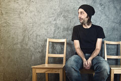 Uomo che si siede sulla sedia di legno e sull'attesa Fotografia Stock