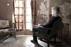 Uomo che si siede sulla sedia di oscillazione fotografie stock