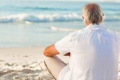 Uomo che si siede sulla spiaggia fotografia stock