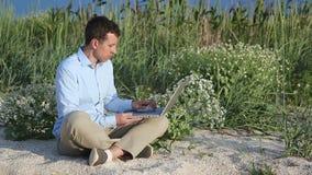 Uomo che si siede sulla spiaggia con un computer portatile archivi video
