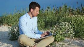 Uomo che si siede sulla spiaggia con un computer portatile freelance video d archivio