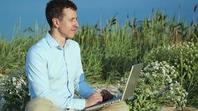 Uomo che si siede sulla spiaggia con un computer portatile freelance stock footage