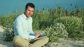 Uomo che si siede sulla spiaggia con un computer portatile freelance archivi video
