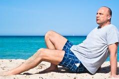 Uomo che si siede sulla spiaggia per rilassarsi Fotografie Stock