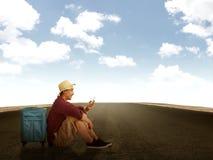 Uomo che si siede sulla strada facendo uso del suo cellulare Fotografia Stock Libera da Diritti
