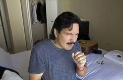 Uomo che si siede sulla tosse del letto Immagine Stock