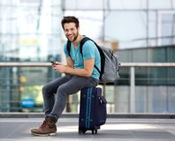 Uomo che si siede sulla valigia e che invia messaggio di testo Fotografia Stock
