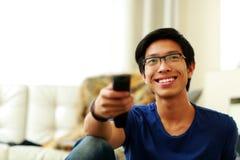Uomo che si siede sullo strato che guarda TV a casa Fotografia Stock