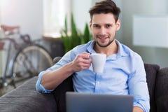 Uomo che si siede sullo strato con il computer portatile Fotografia Stock Libera da Diritti