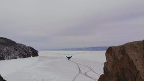 Uomo che si siede in un'amaca montata ad elevata altitudine sopra un lago congelato video d archivio