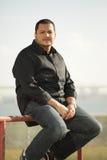 Uomo che si siede in un ambiente urbano Fotografie Stock Libere da Diritti