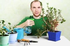 Uomo che si siede vicino alla tabella con la strumentazione di giardinaggio Immagine Stock