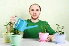 Uomo che si siede vicino alla tabella ed alle piante di innaffiatura Fotografia Stock Libera da Diritti