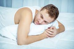 Uomo che si trova al letto Fotografia Stock Libera da Diritti