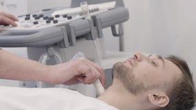 Uomo che si trova durante subire sistema diagnostico di ultrasuono per la tiroide video d archivio
