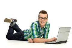 Uomo che si trova giù per mezzo del computer portatile Immagine Stock