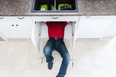 Uomo che si trova sul pavimento sotto il lavandino di cucina che ripara una perdita fotografia stock libera da diritti