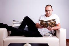 Uomo che si trova sul sofà Fotografia Stock