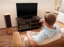 Uomo che si trova sul sofà che guarda TV Fotografia Stock