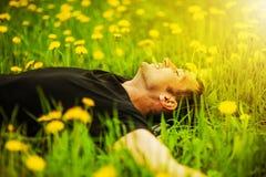 Uomo che si trova sull'erba al giorno soleggiato Immagini Stock Libere da Diritti