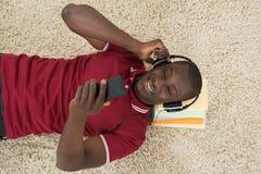 Uomo che si trova sulla pila di musica d'ascolto dei libri sulle cuffie Fotografia Stock Libera da Diritti