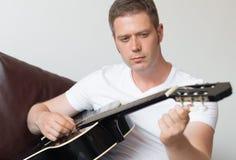 Uomo che sintonizza una chitarra fotografia stock