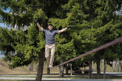 Uomo che slacklining al giorno soleggiato Fotografie Stock