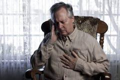 Uomo che soffre con i dolori della testa e del petto Immagini Stock Libere da Diritti