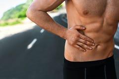 Uomo che soffre dal mal di stomaco dopo avere corso all'aperto Lesione di sport Fotografia Stock