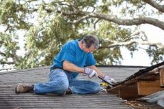 Uomo che solleva legno marcio dai fasci di tetto e dal Decking fotografia stock libera da diritti