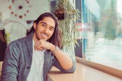 Uomo che sorride esaminandovi macchina fotografica a casa immagini stock libere da diritti