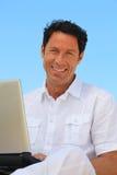 Uomo che sorride sul computer portatile Immagine Stock