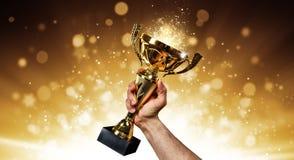 Uomo che sostiene una tazza del trofeo dell'oro Immagini Stock