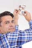 Uomo che sostituisce batteria in sensore di fumo domestico immagine stock libera da diritti