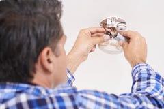 Uomo che sostituisce batteria in sensore di fumo domestico immagini stock libere da diritti