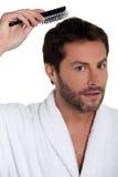 Uomo che spazzola i suoi capelli Immagine Stock Libera da Diritti
