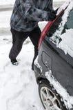 Uomo che spinge automobile attaccata in neve Fotografie Stock Libere da Diritti